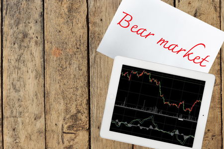 bear market: Paper with bear market text and tablet with graph on wood table