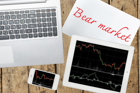 bear market: Smartphone, computer, paper with bear market text and tablet with graph on wood table Stock Photo