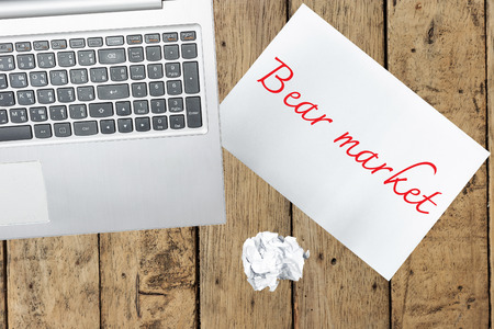 bear market: Computer and paper with bear market on wood table Stock Photo