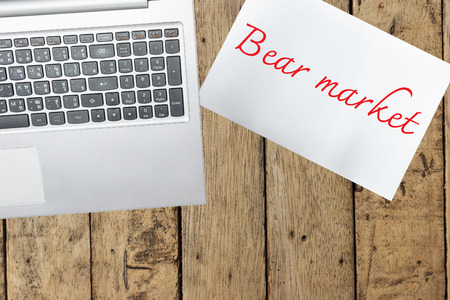 bear market: Computer, paper with bear market on wood table