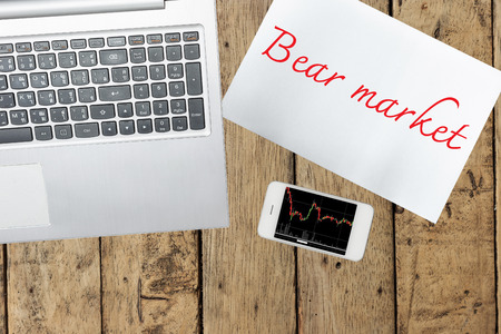 bear market: Computer, paper with bear market text and smartphone with graph on wood table