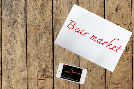 bear market: Smartphone, paper with bear market on wood table Stock Photo