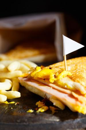 sandwish: Sandwish ham cheese with frenchfries on wood plate and black background