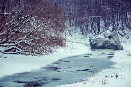tanque de guerra: tanque postrado bajo la nieve. Destruir los tanques de un río congelado Foto de archivo