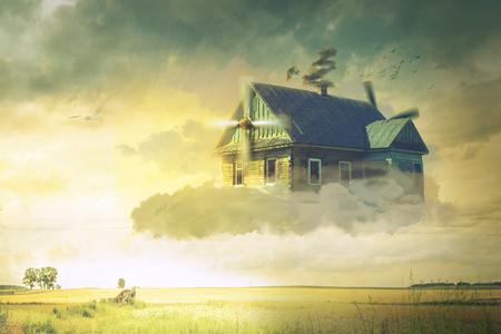 Het huis in de wolken zwevend boven de grond Stockfoto