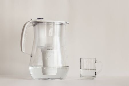Purified water in a jug with a filter and a transparent glass