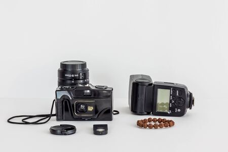 Film camera, lens, external flash and bracelet on an isolated background.