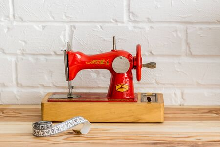 Red sewing machine on a wooden table. Sewing and knitting industry. Diy