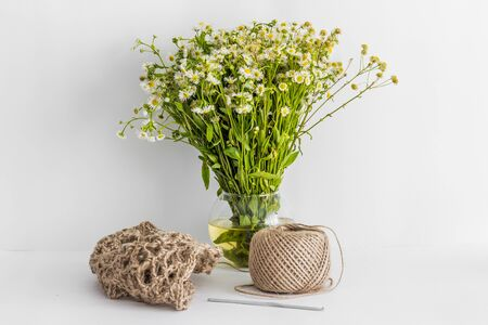 Jute product and a ball of thread against the background of daisies in a vase