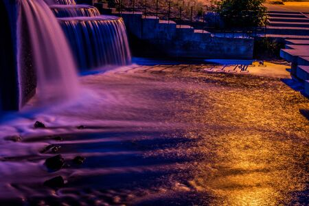 Waterfall and fountains in neon lighting of city lanterns in the late evening