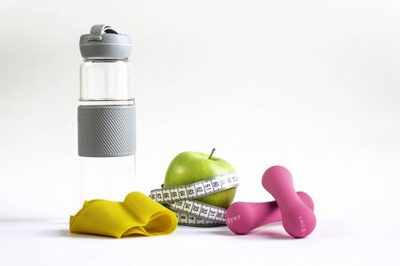 Apple with measuring tape, fitness elastic band, water bottle and dumbbells