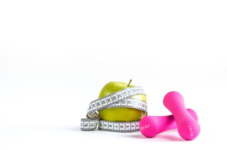 Apple with measuring tape and dumbbells on isolated background