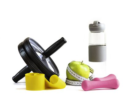 Apple with tape, wheel, fitness elastic band, water bottle and dumbbells