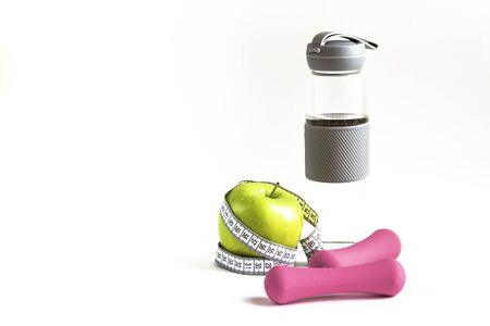 Apple with measuring tape, water bottle and dumbbells on insulated background