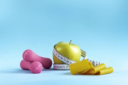 Apple with measuring tape, fitness elastic band and dumbbells Imagens