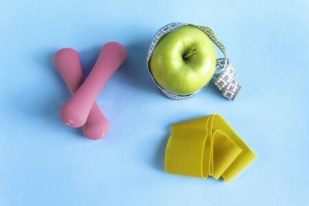 Apple with measuring tape, fitness elastic band and dumbbells 版權商用圖片