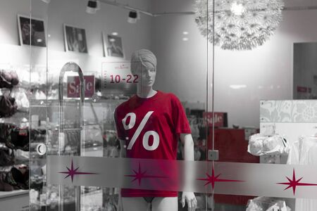 Belarus, Minsk, September 2019: Mannequins in red t-shirts with discount signs behind the glass store 新聞圖片