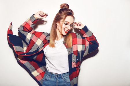 Fashion pretty young woman in glasses over white background. Lifestyle and people concept. Having fun, dance, fly. Portrait of a cheerful fashion hipster girl going crazy in casual colorful hipster clothes with red lips Archivio Fotografico