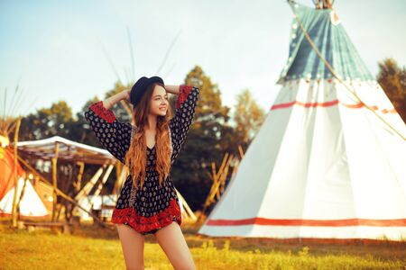 Young beautiful girl smiling on background teepee, tipi- native indian house. Pretty girl in hat with long cerly hair, in dress pouse. Travel in Western. Freedom, smile cute woman. Sunny day.