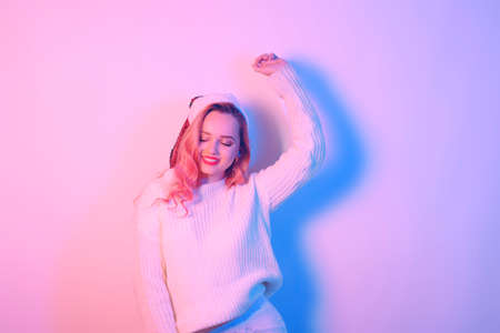 Girl in a white sweater and santa hat in neon light. Woman with professional makeup and red lips. Model with pink hair dancing. New Year Christmas.