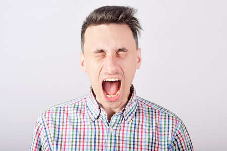 Guy student shouts loudly on white background