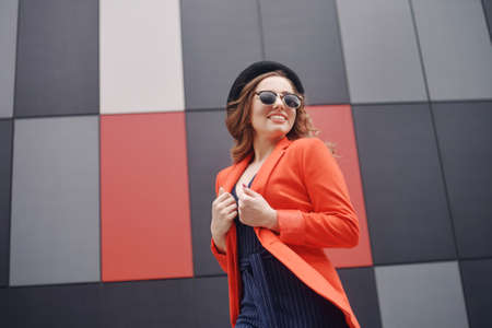 Cute lovely young woman in sunglasses, red jacket, hat, standing over abstract background outdoor. Model girl with long curly hair and perfect smile. Autumn fashion