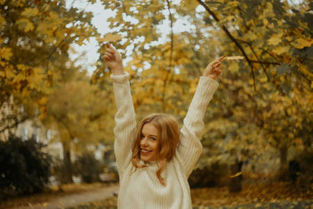 Photo portrait of a girl in a white sweater, the blonde holds leaves in her hands. Pretty woman in the park in autumn. Autumn fashion and style. Warm mood