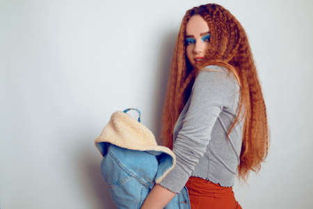 A girl with curled voluminous hair is dancing, a model in the style of the 80s. 90s, with bright blue make-up and a jacket. The girl on a white background sobazet, flirts. Fashion photo of a model in the old style.