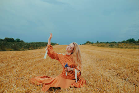 A beautiful girl in a dress sits on a wheat field. Fabulous photo of a blonde outside the city. A woman without allergies holds blue flowers.