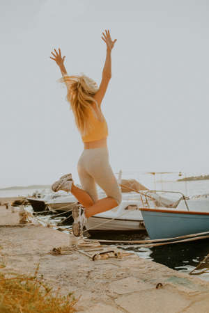 Joyful girl jumps on the background of the sea. Vacation, freedom. Woman on the background of yachts and ships