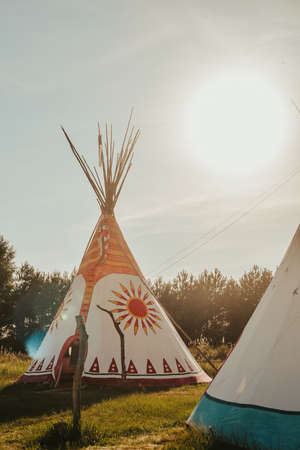Tipi house in the forest against the background of trees, camping, village in the forest, camping. Indian teepee house at sunset.