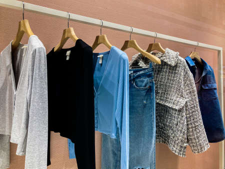 Clothes on hangers in the store. Basic wardrobe sweatshirts hanging on a hanger