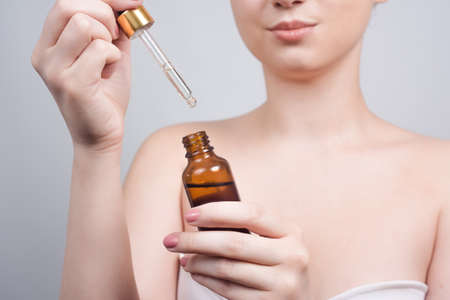 Close up of pretty brunette lady applying cosmetic oil on her face with pipette. Beauty therapy concept. Clean skin and face care. Youth and cosmetics Stockfoto