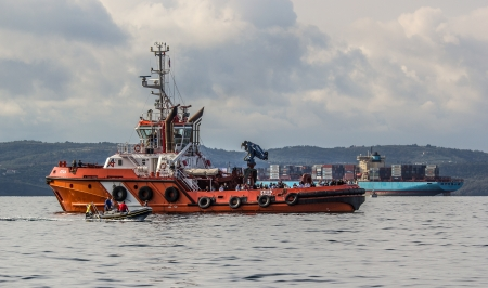 Orange tugboat in action during Barcolana 2012, gulf of Trieste, Italy Editorial