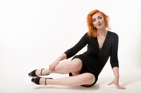 beautiful redhead girl in a black dress on a white background