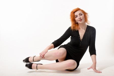 skirts: chica pelirroja hermosa en un vestido negro sobre un fondo blanco