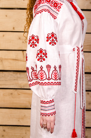 embroidered: Ukrainian embroidered female folk costume  background wood Stock Photo