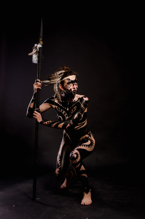 animal woman: girl painted with black paint in the image of warrior women on a black background