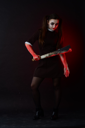 diabolic: Portrait of a young girl with knife, fork and and a piece of raw meat on a plate. Girl in school uniform as killer. The image in the style of Halloween