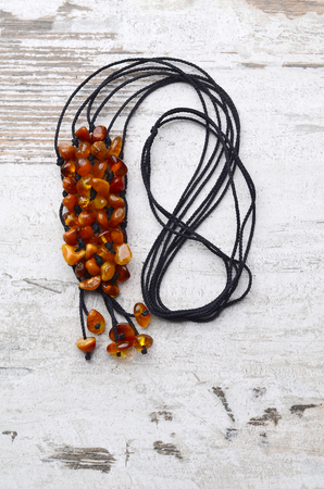 Bright orange amber necklace of raw beads Necklace of amber beads Amber beads string on an old gray wooden background Stock Photo