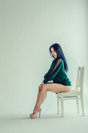 Semi-nude beautiful girl posing on a chair in a classic suit.