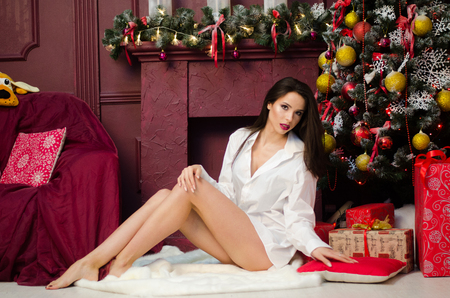 Portrait of beautiful sensuality girl in jeans shirt, sitting on bed, posing, smiling, relaxing. Loft interior of cozy bedroom decorated for Christmas and holidays, party night. Home comfort.