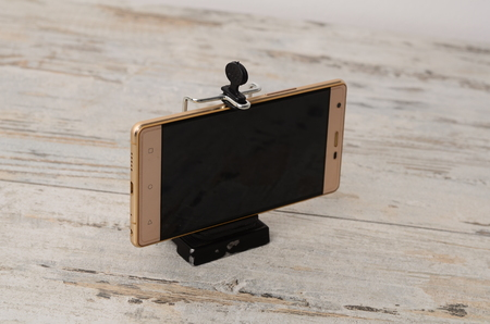 Car holder for mobile device on wood background .