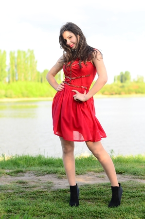 Happy smile girl on the beautiful old city square dancing in the rain, wears stylish red velvet short dress