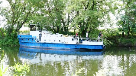 Ukraine, Lutsk 27.06.18 clearing of the river bed of Styr, a boat, a barge, an ekskovator