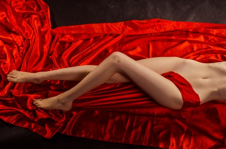 Pretty legs with red silk and black background.