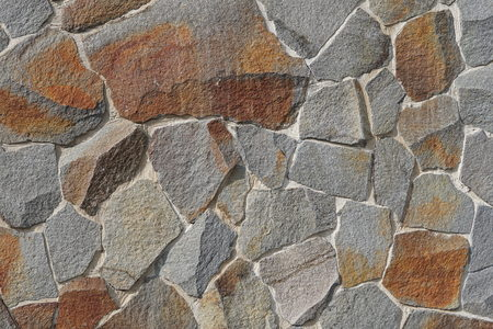 Decorative wall of artificial torn stone in brown tones. Stone masonry in geometric pattern as background or texture Foto de archivo