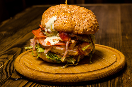 Bacon burger with beef patty on wooden table.