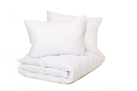 Rolled white duvet cover on white isolated background Stock Photo