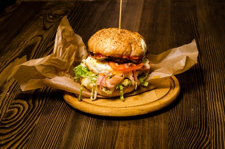 Bacon burger with beef patty on wooden table. Banque d'images - 122684460
